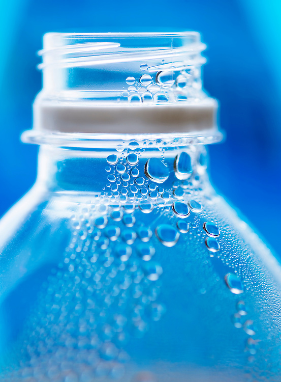 The top of a plastic water bottle with water droplets inside the bottle.  Blue background.