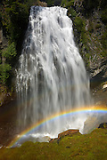 A bright rainbow forms at the base of Narada Falls, a popular waterfall along the Wonderland Trail in Mount Rainier National Park, Washington. At Narada Falls, the Paradise River drops 168 feet (51 meters). Narada is a Hindu word meaning uncontaminated or pure.