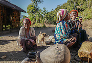 Tatooed Chin women smoke outside their home in rural Chin State, Myanmar.