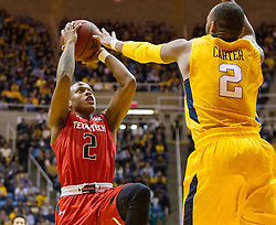 Mar 2, 2016; Morgantown, WV, USA; Texas Tech Red Raiders guard Devon Thomas (2) attempts to shoot over West Virginia Mountaineers guard Jevon Carter (2) during the first half at the WVU Coliseum. Mandatory Credit: Ben Queen-USA TODAY Sports
