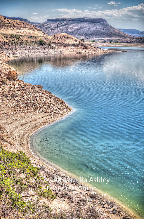 Curved shoreline of reservoir beneath panoramic blue mesa. Curecanti National Recreation Area, Gunnison, Colorado.  HDR rendering accentuates luminescent colors of the landscape/waterscape.