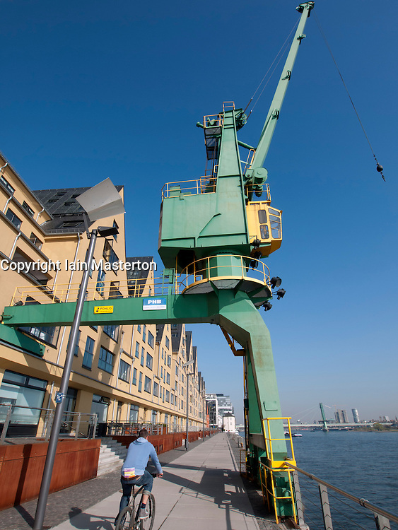 Old dock crane and renovated former warehouse now apartments in Rheinaufhafen area of Cologne Germany