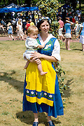 Woman dressed in Swedish costume holding baby. Svenskarnas Dag Swedish Heritage Day Minnehaha Park Minneapolis Minnesota USA