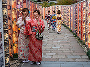 The colorful Kimono Forest art installation lines a lane to Randen Arashiyama tram station on Keifuku Arashiyama line, in Kyoto, Japan. This artwork of 600 pillars was installed by Yasumichi Morita in 2013 using 32 different patterns of textiles dyed in the traditional Kyo-yuzen style, created by Kamedatomi, a textile factory whose history dates back to Taisho period.