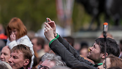 © Licensed to London News Pictures. 02/05/2015. London, UK. A man takes a photo in the crowd, as in keeping with tradition, the royal birth announcement of the Duke and Duchess of Cambridge's second child, a daughter, born at 8.34am, today, 2 May 2015, is posted on an easel outside Buckingham Palace.  The document is signed by the the delivery team at St Mary's Hospital in Paddington - led by Alan Farthing, the royal surgeon-gynaecologist . Photo credit : Stephen Chung/LNP