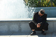 Ashgabat, Turkmenistan - 2017 September 19: Man sleeps near the fountain at the Olympic Sport Complex while 2017 Ashgabat 5th Asian Indoor & Martial Arts Games on September 19, 2017 in Ashgabat, Turkmenistan.<br /> <br /> Mandatory credit:<br /> Photo by © Adam Nurkiewicz<br /> <br /> Adam Nurkiewicz declares that he has no rights to the image of people at the photographs of his authorship.<br /> <br /> Picture also available in RAW (NEF) or TIFF format on special request.<br /> <br /> Any editorial, commercial or promotional use requires written permission from the author of image.