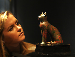 A Christie's employee looks at a bronze cat from Egypt circa 664-30 BC estimated at £40,000-60,000 at the Antiquities at Christie's  pre auction display in London, England. Monday, 21st October 2013. Picture by Max Nash / i-Images