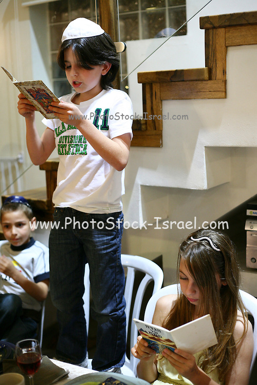 "An israeli family attending a ""Seder"",  the traditional passover dinner,  and reading the ""Hagada"" (the story of israeli's exodus from Egypt)  during the evening. Children reading the Hagadah"