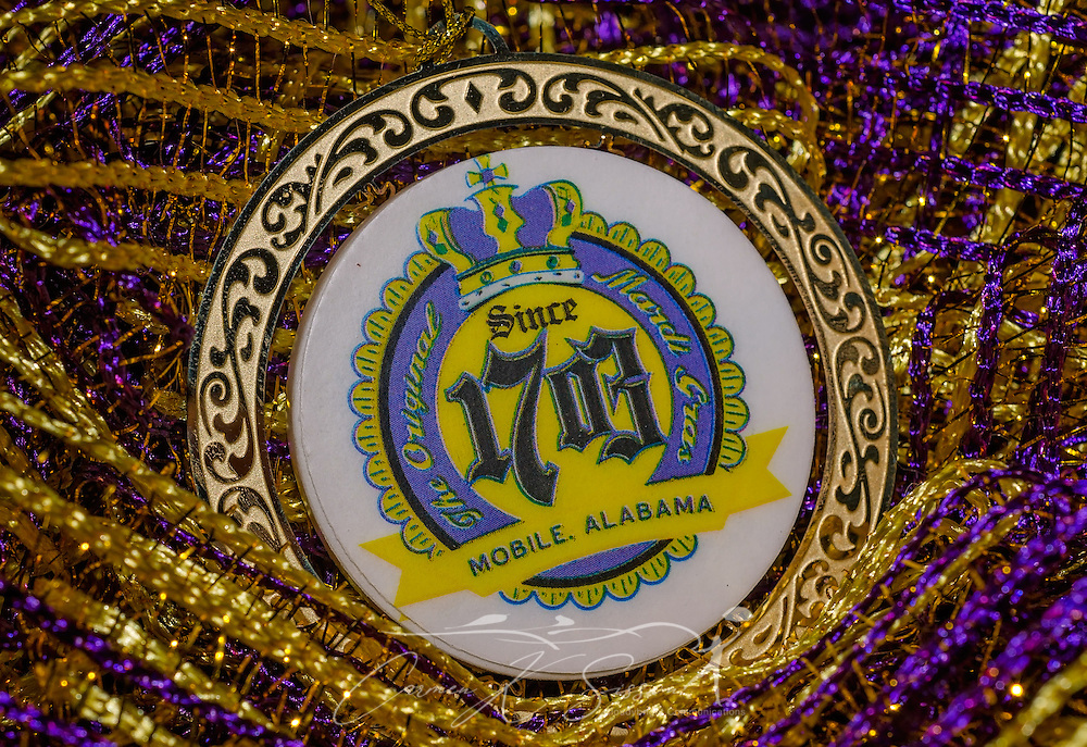 A gold medallion proclaims Mobile, Alabama as the home of the first, original Mardi Gras, a tradition dating back to 1703. The city of New Orleans also claims to be the home of the first Mardi Gras. Historians believe that French-Canadian explorers Pierre Le Moyne d'Iberville and Jean-Baptiste Le Moyne de Bienville arrived in Louisiana in 1699, naming a point south of Louisiana Pointe du Mardi Gras. Bienville founded the city of Mobile in 1702, and in 1703, Mobile's French settlers celebrated the city's first Mardi Gras. Mardi Gras traditionally begins on January 6, the Feast of the Epiphany, and ends the day before Ash Wednesday. It has become known as a time of revelry and, sometimes, debauchery, preceding the 40 days of Lent before Easter Sunday. Though Mardi Gras was originally a Catholic holiday, many non-Catholics now enjoy the sights and sounds of the season. The traditional colors are purple, green, and gold, symbolizing justice, faith, and power. (Photo by Carmen K. Sisson/Cloudybright)