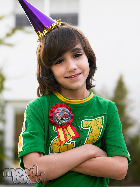 Portrait of boy (10-12) in party hat smiling arms crossed