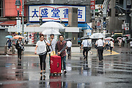Tourist walking under the rain. Typhoon number 10 called Lionrock hit japan early on morning, in Tokyo. 30/08/2016-Tokyo, JAPAN