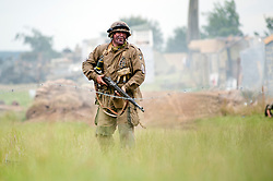 A Sargent from the US 101st Airborne advances across open ground towards enemy positions during a battle reenactment at the Ponderosa Wartime Weekend Heckmondwike<br /> 10th July 2011<br /> Images © Paul David Drabble