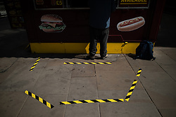 © Licensed to London News Pictures . 20/05/2020 . Manchester , UK . Yellow and black tape marks social distancing lines on the pavement outside a hotdog stall on Market Street in Manchester City Centre . On the hottest day of the year so far independently run coffee shops and bars are open and trading with social distancing measures applied , after a period of being shut in an effort to reduce the spread of Covid-19 . Photo credit : Joel Goodman/LNP