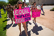 26 MARCH 2012 - PHOENIX, AZ: JENNA DUFFY leads a march of topless women and men in Phoenix. About 40 people marched through central Phoenix Sunday to call for a constitutional amendment to give women the same right to go shirtless in public that men have. The Phoenix demonstration was a part of a national Topless Day of Protest. Phoenix prohibits women from going topless in public so protesters, women and men, covered their nipples and areolas with tape. The men did it to show solidarity with the women marchers.  PHOTO BY JACK KURTZ