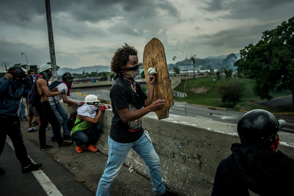 CARACAS, VENEZUELA - MAY 10, 2017:  Anti-government protesters with homemade shields take cover from rubber bullets and buckshot being shot at them as they fight to take control of Francisco Fajardo highway from National Guard soldiers. The streets of Caracas and other cities across Venezuela have been filled with tens of thousands of demonstrators for nearly 100 days of massive protests, held since April 1st. Protesters are enraged at the government for becoming an increasingly repressive, authoritarian regime that has delayed elections, used armed government loyalist to threaten dissidents, called for the Constitution to be re-written to favor them, jailed and tortured protesters and members of the political opposition, and whose corruption and failed economic policy has caused the current economic crisis that has led to widespread food and medicine shortages across the country.  Independent local media report nearly 100 people have been killed during protests and protest-related riots and looting.  The government currently only officially reports 75 deaths.  Over 2,000 people have been injured, and over 3,000 protesters have been detained by authorities.  PHOTO: Meridith Kohut
