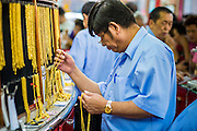 17 APRIL 2013 - BANGKOK, THAILAND:  A salesman in a gold shop in Bangkok gets gold chains for a customer. Thais flocked to gold shops in Bangkoks's Chinatown this morning to buy gold. Wednesday was the first day most gold shops were open after a five day holiday weekend. Shops were closed Friday through Tuesday, when global gold prices dropped by more than 13% based on jitters that Cyprus might liquidate its gold stocks. The Thailand Futures Exchange (TFEX) suspended trading of all gold and silver futures for a short time Tuesday morning because of instability in the market. Gold is now about 22 percent below the record peak of $1,920.30 an ounce set in September 2011. Thais buy gold as both jewelry and an investment, a hedge against inflation and financial failures. Bangkok's Chinatown district is the center of Thailand's gold trade.   PHOTO BY JACK KURTZ