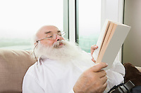 Senior man reading book in house
