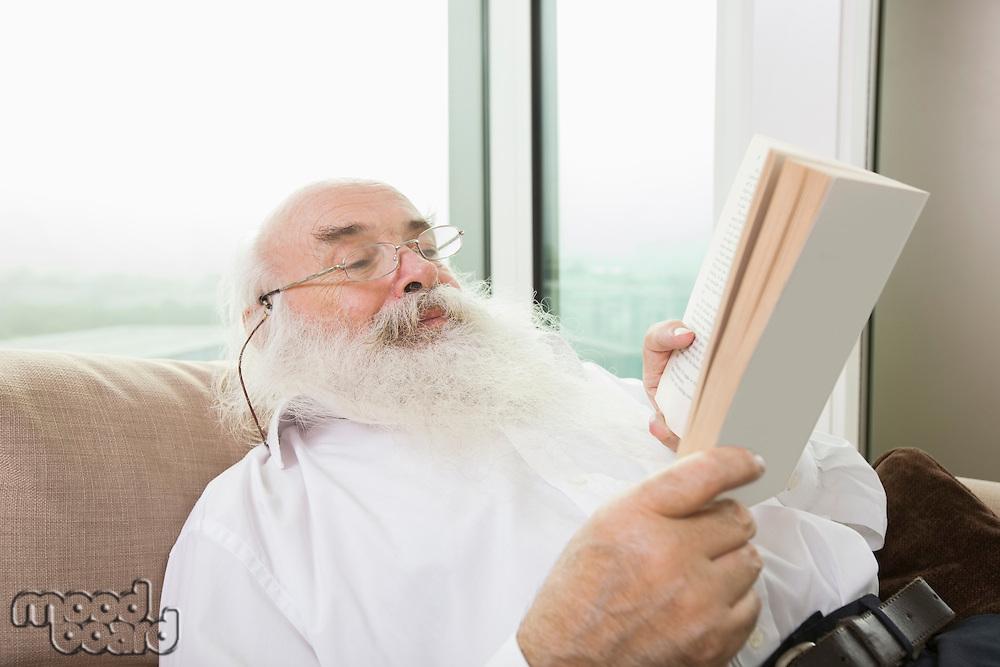 Senior man reading book in house