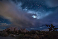 Distant flashes of lightning kept me awake much of the night at Joshua Tree National Park. Finally at 4am, I got up to try to photograph it. I never got any bolts because the lightning was too sporadic. In this image a flash of lightning behind me lit up the rocks, while a smaller storm moves under the moon and stars.<br /> <br /> Date Taken: August 20, 2014
