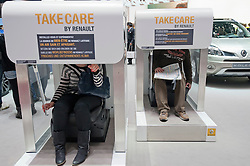 Visitors using Renault Take Care vehicle interior well-being test  simulator at Geneva Motor Show 2011 Switzerland