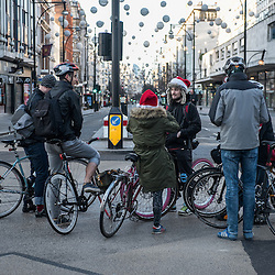 London, UK - 25 December 2014: a group of cyclists stand in the middle of Oxford Circus on early Christmas morning.