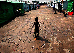GERIHUN, SIERRA LEONE - JULY 18:Liberian refugees walk through their plastic tents  at the Gerihun camp near Bo, Sierra Leone July 18,2002. Sierra Leone is infamous for some of the decade's worst war crimes and the irony is that as Sierra Leonians are finally able to return home, their neighbors across the border are suffering from their own tragic decade old conflict and flooding into the camps which once housed the internally displaced Sierra Leonians. Liberia's rebels have waged an insurgency for three years, but have stepped up attacks recently against President Charles Taylor's government. Taylor, a former warlord who won presidential elections in 1997, says he is being targeted by some of his rivals from the 1989-96 civil war.  The heavy toll on civilians in the fighting poses a threat to the stability of other countries in the region, particularly Sierra Leone. There are about 50,000 refugees in Sierra Leone now according to the World Food Program and 100,000 internally displaced people within Liberia now. Sierra Leone, which has the U.N's largest peacekeeping mission with 17,3000 troops, is recovering from a ruthless 10-year-old war and held presidential elections in May. (photo by Ami Vitale/Getty Images)