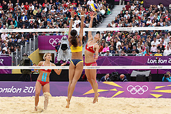 Sara Goller attacks for Germany as Talita Rocha blocks for Brazil during the Women's Beach Volleyball Preliminary Phase Pool E match between Brazil and Germany held at the Horse Guards Parade stadium in London as part of the London 2012 Olympics on the 31st July 2012.Photo by Ron Gaunt/SPORTZPICS