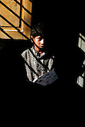 A boy stands in the window light in a primary school in the Khairo Dero village in Larkana, Pakistan, on Wednesday, Jan. 23, 2008. Pakistan is seeking to sustain growth in a country where the government estimates a fourth of the population lives in poverty, or on less than a dollar a day.