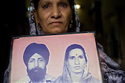 Harjinder Kaur, 57, (right) is showing an old photograph of herself and her husband before his assassination by Hindu mobs, in Tilak Vihar, New Delhi, India. She has lost her husband and other members of her family during the anti-Sikh riots erupted in New Delhi in 1984 in the light of Indira Gandhi's assassination by her Sikh bodyguards.