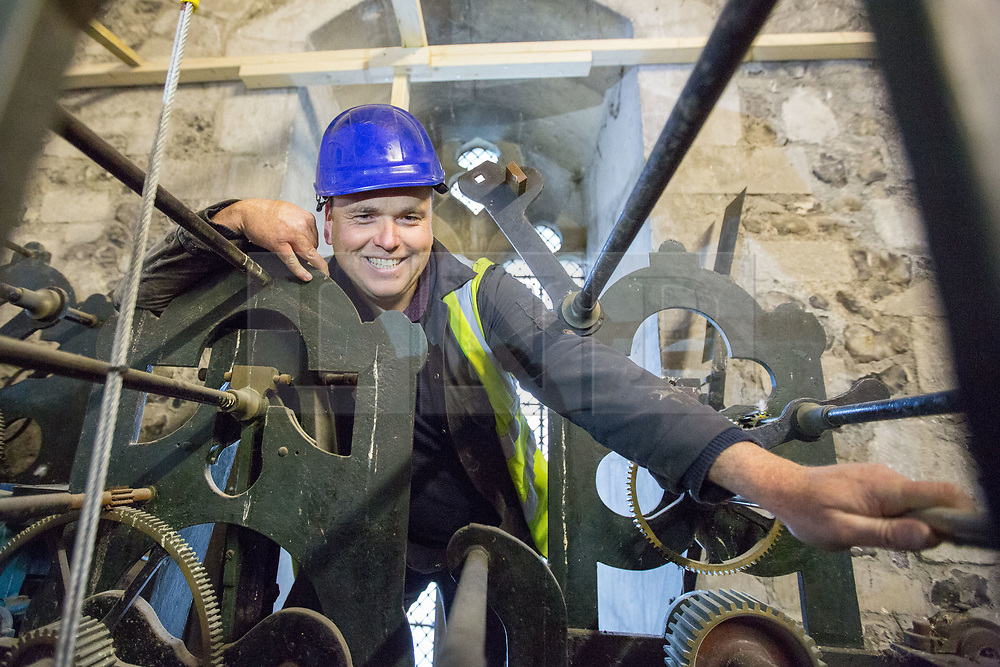 @Licensed to London News Pictures 27/11/2018.Canterbury, Kent. Mark Crangle, clock maker in charge of the removal of the Canterbury Clock face. The Cathedral Clock built in 1855  and housed on the south west tower of Canterbury Cathedral is being dismantled ready to be renovated and re-guilded. The clock face weighing 78 kilos and measuring 8 feet in diameter is being shipped to the Cumbrai Clock Company in Penrith and will be absent from the cathedral for 18 months. Photo credit: Manu Palomeque/LNP