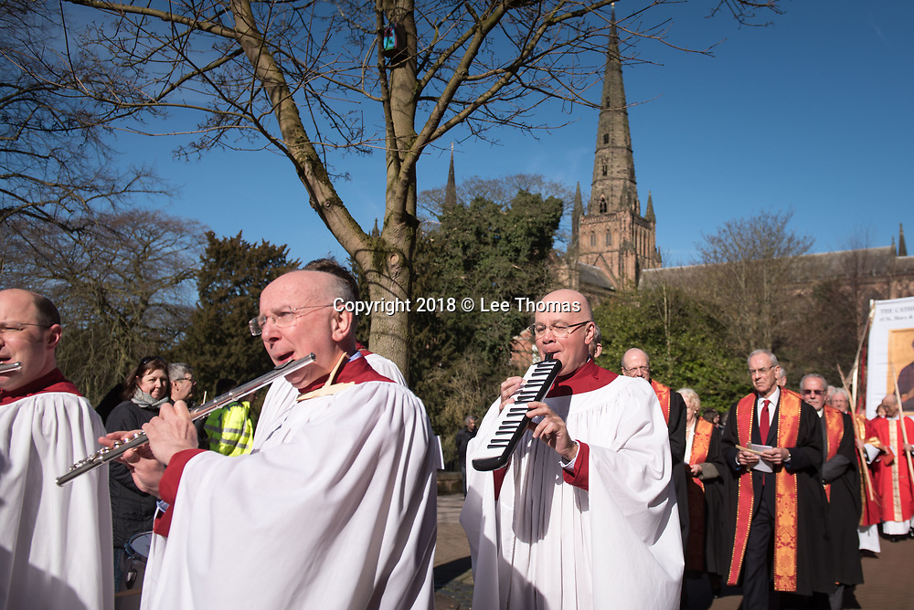 "Lichfield, Staffordshire, UK. 25th March 2018.  A fine spring morning greeted worshipers, members of the clergy and a donkey for the annual Palm Sunday procession through the medieval streets of Lichfield. The ""Triumphal Entry"" procession (when Jesus entered Jerusalem cheered on by a crowd, riding on a donkey) began at Speakers' Corner in the Staffordshire city and ended at the west door of the famous Cathedral. Pictured: Worshippers play instruments as the procession makes its way through the streets of LIchfield. // Lee Thomas, Tel. 07784142973. Email: leepthomas@gmail.com  www.leept.co.uk (0000635435)"