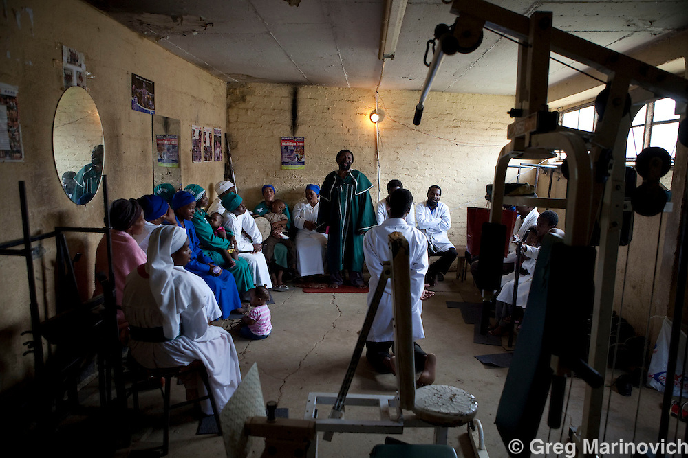 Members of a Zionist or African syncretic church worship in a gymnasium at the Zulu-dominated Madala hostel in the tiny impoverished township of Alexandra in Johannesburg is alongside Sandton, the ultra wealthy business hub of South Africa. Photo Greg Marinovich