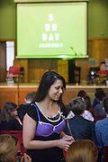 A young woman is wearing a bra on top of her clothes in support of a campaign for beast cancer research, during The Sunday Assembly (today held inside Conway Hall in central London), an atheist service founded by British comedians Sanderson Jones and Pippa Evans in 2013, in London, England. The gathering is designed to bring together non-religious people who want a similar communal experience to a religious church. Satellite assemblies have been established in over 30 cities including New York, San Diego, and Dublin.