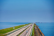 De Afsluitdijk bij Den Oever. In 1932 werd de opening tussen de Waddenzee en de toenmalige Zuiderzee gesloten. Nu is het een belangrijke verkeersader tussen Friesland en Noord-Holland en scheidt het de Waddenzee (links) met het IJsselmeer.<br /> <br /> The Afsluitdijk near Den Oever. In 1932, the gap between the Wadden Sea and the former Zuiderzee closed by the Afsluitdijk. Now it is a major thoroughfare between Friesland and North Holland and it separates the Wadden Sea from the IJsselmeer.