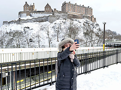 Pictured: Tourist Evita Chrysostomou (29) from Greece takes a minute to get a selfie in front of a snow-covered Edinburgh Castle. on Thursday morning.<br /> <br /> The severe winter weather continued to cause chaos throughout Scotland, with the most severe level of Amber warning being extended until 10am on Friday 02 March.<br /> <br /> © Dave Johnston / EEm