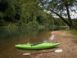 A kayak rests at a tranquil beach on the Current River located within the Ozark National Scenic Riverways. The Current River is the most spring-fed of all the rivers in the Missouri Ozarks. The river is a favorite with paddlers who enjoy the cold crystal clear water from springs that feed the Current River, including Cave Spring, Pulltite Spring, Round Spring, Blue Spring, and Big Spring. The scenic river is lined with rock ledges, caves, gravel bars and bluffs.<br /> <br /> The Ozark National Scenic Riverways was established in 1964, making it America's first national park area to protect a wild river system. The Ozark National Scenic Riverways, which include the Current and Jacks Fork rivers, is known for its caves, springs, sinkholes and losing streams. Visitors can enjoy water activities, such as floating, canoeing, tubing, swimming, and fishing. Additionally, there are opportunities for hiking, horseback riding, and wildlife viewing. Over 130 miles of waterways and 300 identified caves exist within the park.