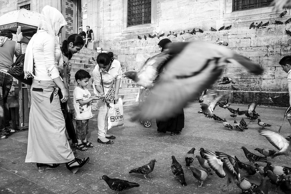 Children feeding pigeons near Istanbul's New Mosque.