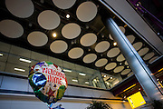 A helium-filled Welcome Home balloon of a family waiting for loved-ones floats in the air in Heathrow Airport's T5