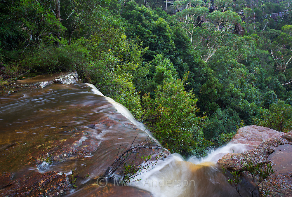 Water rushing over the top of Kelly's Falls, a waterfall in  Garawarra State Conservation Area, near Stanwell Tops, NSW, Australia