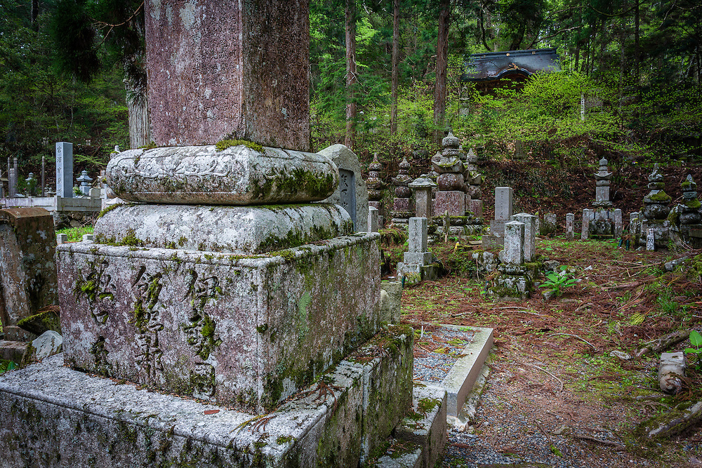A mausoleum hides behind a small hill with trees, in the middle of Okunoin.