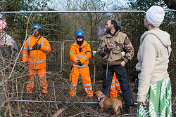Harefield, UK. 7 February, 2020. Activists monitor HS2 engineers in the process of erecting Heras fencing to surround three environmental activists from Extinction Rebellion who have climbed a veteran oak tree close to the Harvil Road wildlife protection camp in order to try to protect it from felling. HS2 are expected to try to fell large numbers of mature trees in the immediate vicinity over the weekend even though the high-speed rail link is still awaiting Boris Johnson's approval.