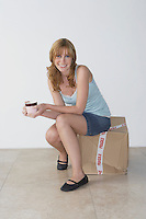 Woman sitting on box in new home portrait