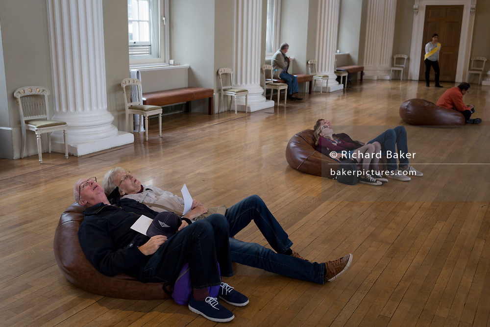 Visitors lie on bean bags to view the paintings above by Paul Rubens on the ceiling of Banqueting House, on 17th September 2017, in Whitehall, Westminster, London, England.