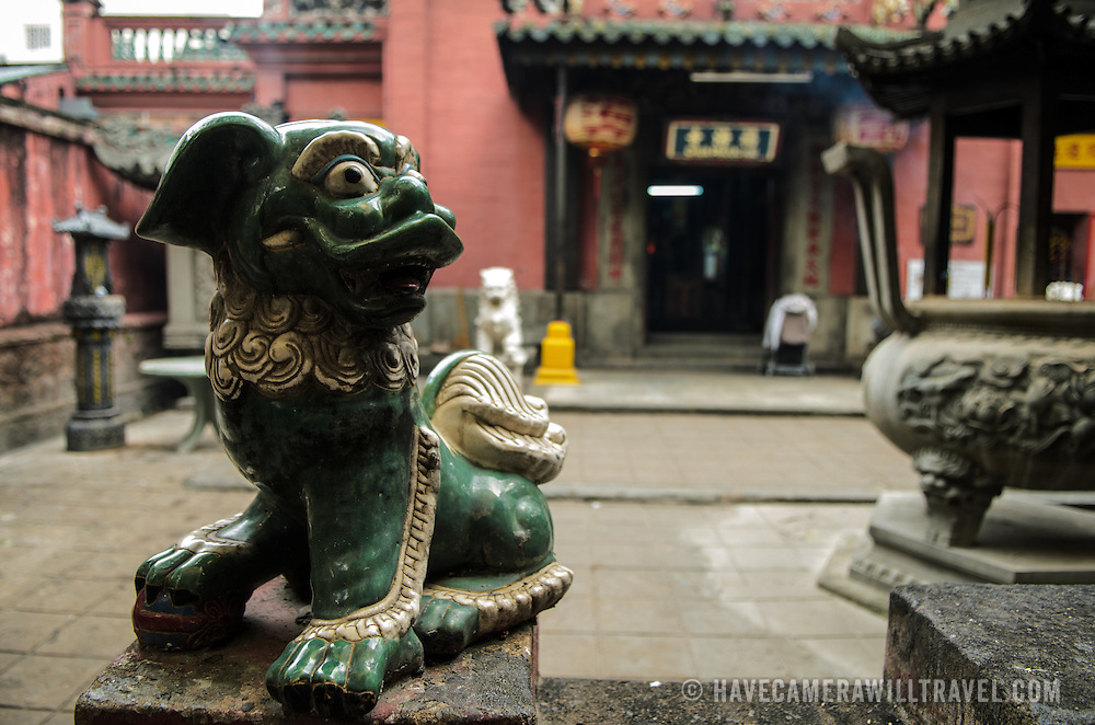 A small green dog stands guard outside the entrance to the Jade Emperor Pagoda in the Da Kao district of Ho Chi Minh City, Vietnam. The Chinese temple was built in 1909 and contains elements of both Buddhist and Taoist religions.