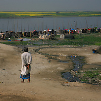 "A man stands watch over a row of bedey dwellers on the bank of the Buruganga River near Dhaka, Bangladesh, Dec. 21, 2009. The waterways of Bangladesh are home to nearly 800,000 ""river gypsies"" or bedey (as they are known locally) that navigate along Bangladesh's network of over 700 rivers and canals on their hand-constructed bamboo houseboats."