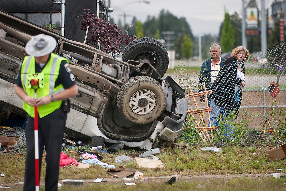 Roger Webb (Left), a sculptor and fence mender, and his wife, Lenore, survey the damages to the Art and Home Center in Coeur d'Alene from an overturned pick-up truck on Friday as a trooper with the Idaho State Police works the scene. The driver, who lost control of his vehicle on Appleway Avenue, needed to be extricated  from the vehicle before being transported to Kootenai Medical Center.