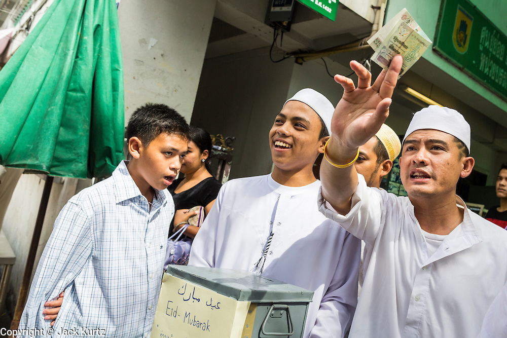"08 AUGUST 2013 - BANGKOK, THAILAND: Thai Muslim men ask for donations for Haroon Mosque after Eid al-Fitr services at the mosque. Eid al-Fitr is the ""festival of breaking of the fast,"" it's also called the Lesser Eid. It's an important religious holiday celebrated by Muslims worldwide that marks the end of Ramadan, the Islamic holy month of fasting. The religious Eid is a single day and Muslims are not permitted to fast that day. The holiday celebrates the conclusion of the 29 or 30 days of dawn-to-sunset fasting during the entire month of Ramadan. This is a day when Muslims around the world show a common goal of unity. The date for the start of any lunar Hijri month varies based on the observation of new moon by local religious authorities, so the exact day of celebration varies by locality.      PHOTO BY JACK KURTZ"