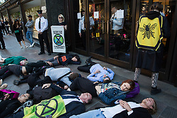 London, UK. 14 May, 2019. Climate change activists from Extinction Rebellion stage a die-in outside Harrods as part of a protest against fast and unsustainable fashion. A small number of activists also succeeded in holding a die-in inside the department store in spite of additional security checks at all entrances.News