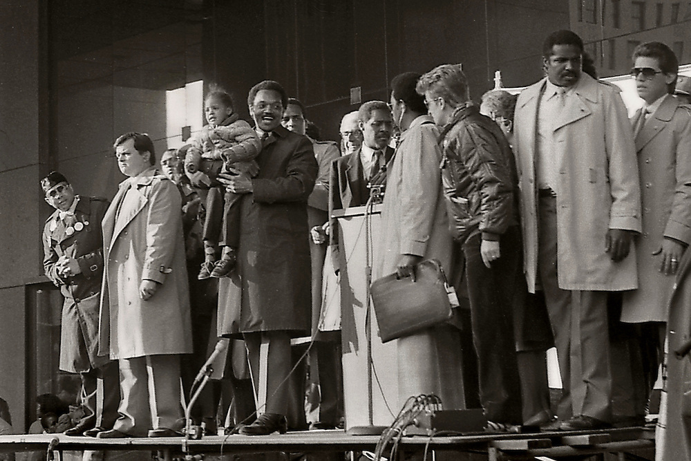 "From the ""Jesse Jackson Harlem Rally"" in 1984. Jesse was running for president. Here he holds up a child taken from the crowd. To his immediate right is Reverend Herbert Daughtry. To the far left is the head of The Nation of Islam in New York. Carl McCall is immediately behind Mr. Jackson."