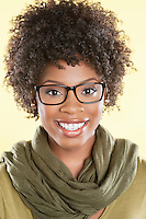 Portrait of a happy African American woman wearing glasses with a stole round her neck over colored background